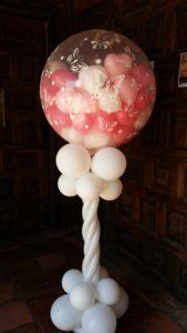 Globo de helio grande con globos en interior sobre columna de globos