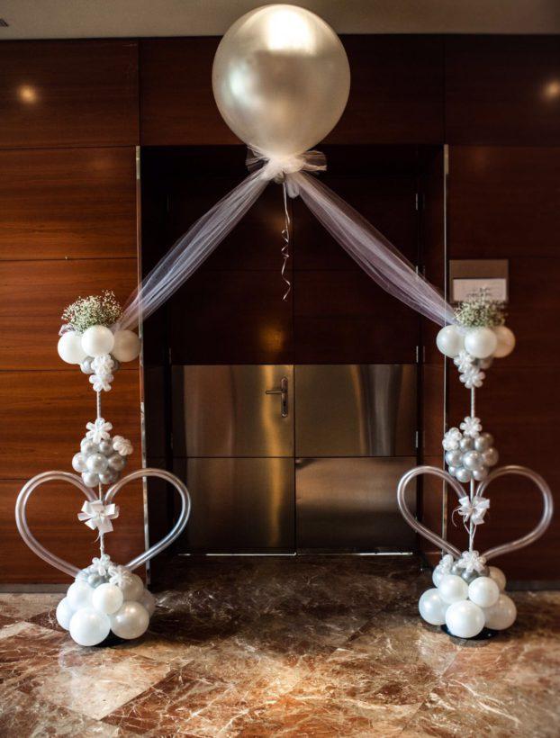 Arco de globos con helio sobre columnas de corazones